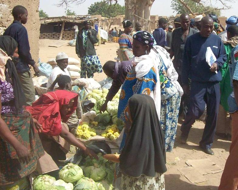 Women buying fresh green vegetables at a West African market
